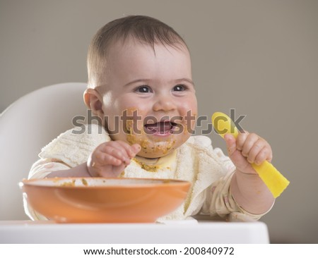 beautiful baby girl laughing during meal time, holding a spoon - stock photo