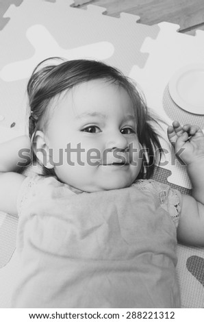 Beautiful baby girl lying down with cute facial expression looking at camera black and white edition - stock photo