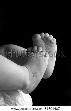 Beautiful baby girl lying down with feet up black and white