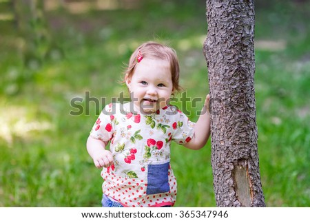 Beautiful baby girl playing on the playground in summer outdoor
