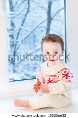 Beautiful baby girl sitting next to a window to a snowy garden on Christmas day - stock photo