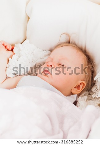 Beautiful baby girl sleeps in bed.  11 month old