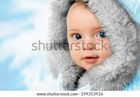 Beautiful baby girl wearing a winter fur coat.