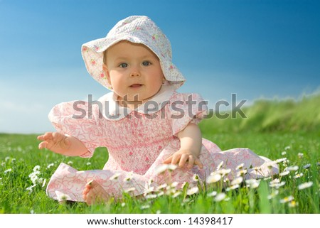 Beautiful baby girl wearing bonnet sat in field of flowers under blue sky. - stock photo