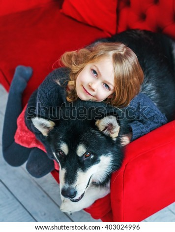 Beautiful baby girl with a big dog on a red sofa