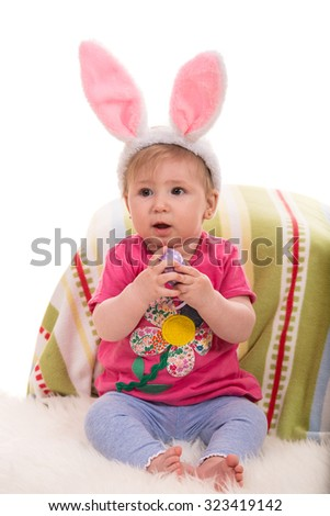 Beautiful baby girl with bunny ears holding Easter egg - stock photo