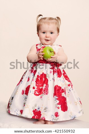 Beautiful baby girl with green apple on a light background. Retro toning - stock photo