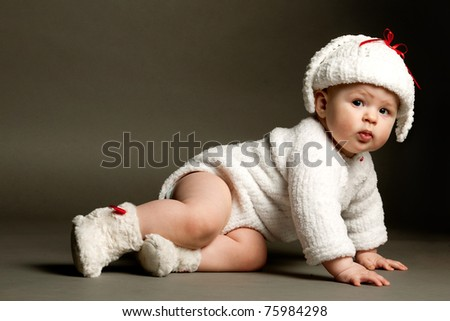 beautiful baby in a knit dress and cap - stock photo