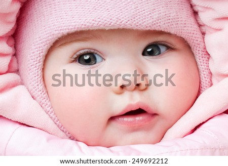Beautiful baby in a pink hat. Winter season - stock photo
