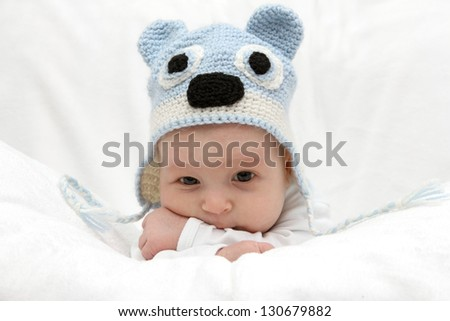 Beautiful baby in  blue hat on the bed - stock photo