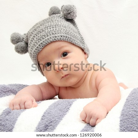 Beautiful baby in gray knitted hat - stock photo
