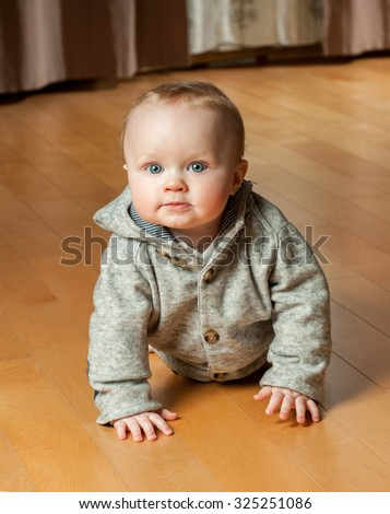 Beautiful baby in the interior. Baby crawling on the floor. - stock photo