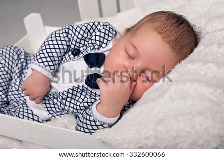 beautiful baby in the New Year's cap and white body sits  - stock photo