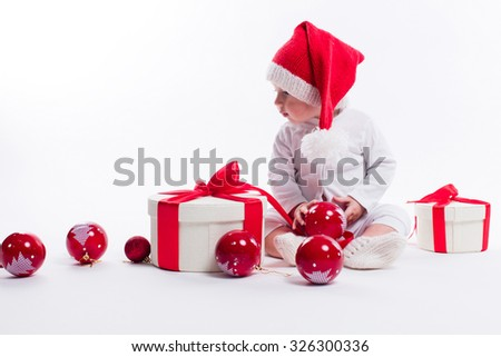 beautiful baby in the New Year's cap and white body sits among boxes of holiday gifts and Christmas balls, picture with depth of field - stock photo
