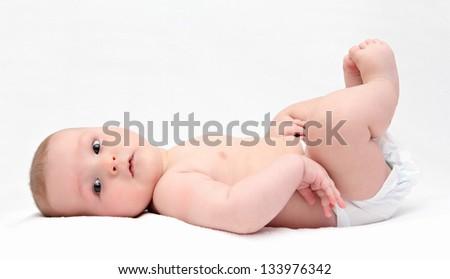 Beautiful baby lies on back - stock photo