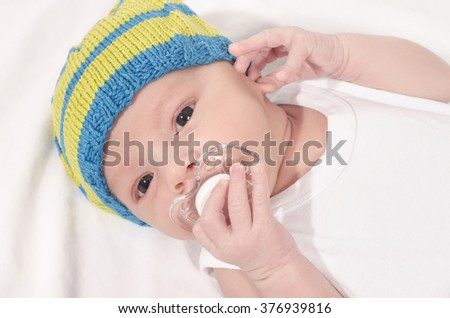 Beautiful baby lying down on white sheets with a pacifier in his mouth. Cute new born baby boy wearing a hat holding a binky.