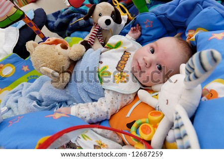Beautiful baby lying in bed surrounded by many toys - stock photo