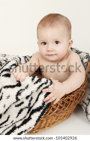 Beautiful baby portrait with cute facial expression sitting in a basket - stock photo