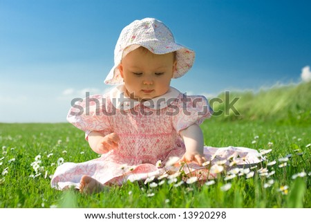 Beautiful baby sat in field looking at flowers. - stock photo