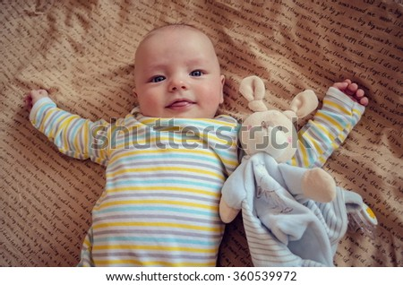 Beautiful baby showing tongue, lying on the bed with a toy mouse. Sweet babies. - stock photo