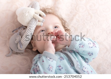 Beautiful baby with a lovely toys.The child in the crib