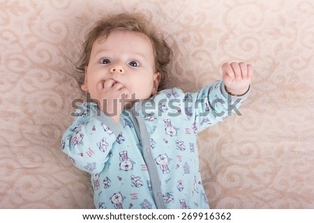 Beautiful baby with a lovely toys.The child in the crib - stock photo
