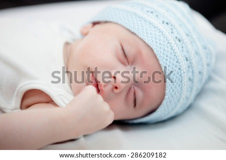 Beautiful baby with blue cap sleeping peacefully - stock photo