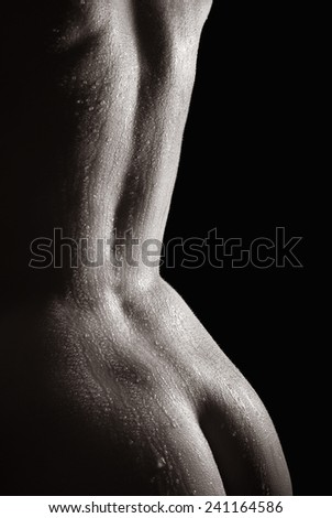 Beautiful back of a nude woman with wet body, monochrome closeup in front of black background - stock photo