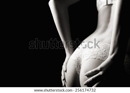 Beautiful back of a woman wearing white panties and bra in front of dark studio  background, monochrome photo with copy space on the left side of the image - stock photo