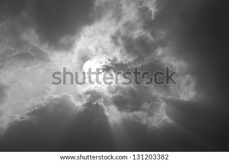 Beautiful background - black and white sunset sky, bright sun shines through clouds - stock photo