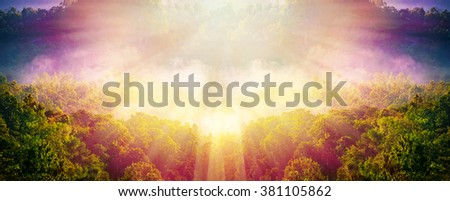 Beautiful background - bright red green yellow sunrise over dark clouds, glowing horizon.Forest with sun flare - stock photo