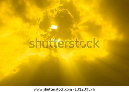 Beautiful background - gold or yellow sunset sky, bright sun shines through clouds - stock photo