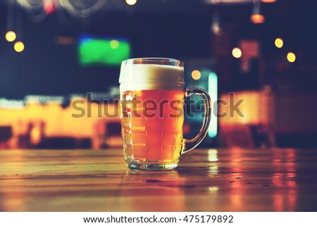 Beautiful background of the Oktoberfest. Glass of cold fresh lager beer on a wooden bar counter in pub with free space for your text. Blue toned