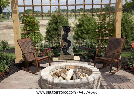 Beautiful backyard with a cozy fire pit and fountain - stock photo