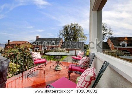 Beautiful balcony with pink pillows after the rain. - stock photo