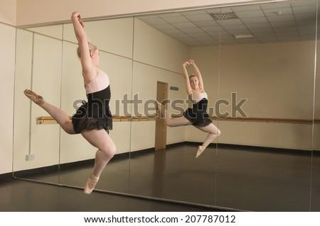 Beautiful ballerina dancing in front of mirror in the dance studio - stock photo