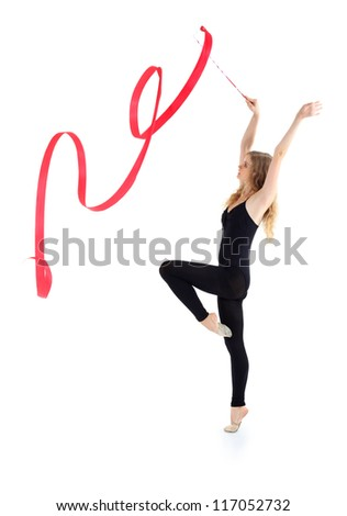 Beautiful ballerina in black suit with red ribbon stands on tiptoe on one leg and raises hands up isolated on white background.