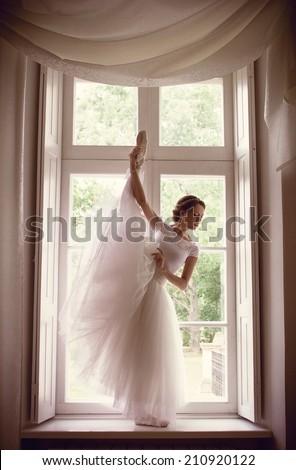 Beautiful ballerina posing near the window - stock photo
