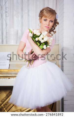 Beautiful ballerina with flowers in the studio