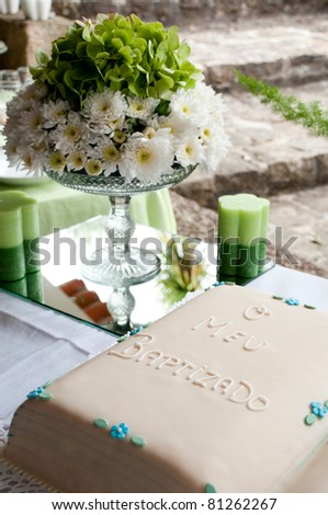 beautiful baptism or christening cake with a gorgeous flowers arrangement and candles (all in green colours) - stock photo