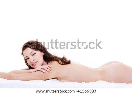 Beautiful bare body of a pretty young happy woman lying down on bed and looking at camera - stock photo