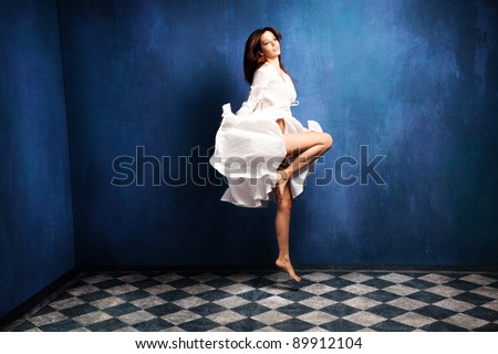 beautiful barefoot woman in white dress levitate in room - stock photo