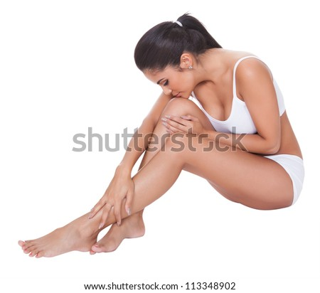 Beautiful barefoot woman sitting on the floor with her long shapely legs crossed in front of her wearing her lingerie - stock photo