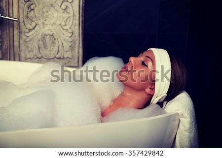 Beautiful bathing woman relaxing in bathtub. - stock photo