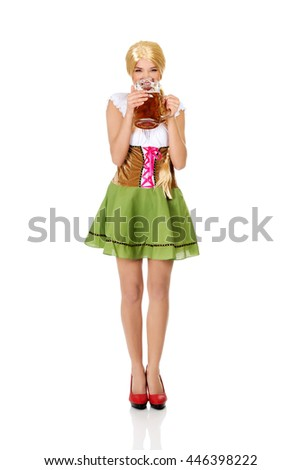 Beautiful bavarian woman drinking beer. - stock photo