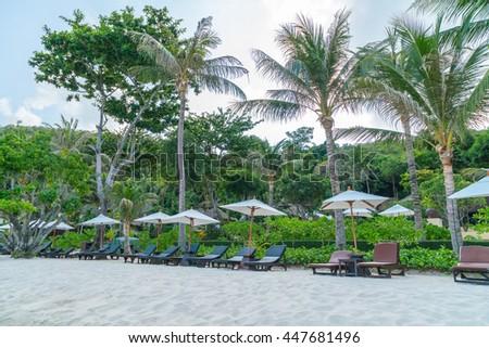 Beautiful beach chairs with umbrella on tropical white sand beach - stock photo