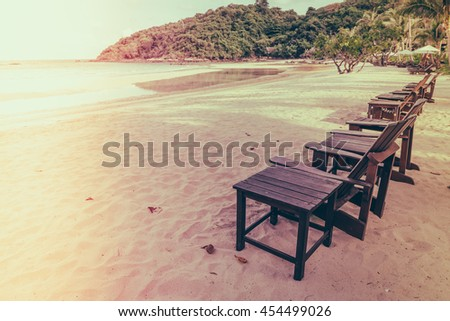 Beautiful beach chairs with umbrella on tropical white sand beach - Filtered image processed vintage effect - stock photo