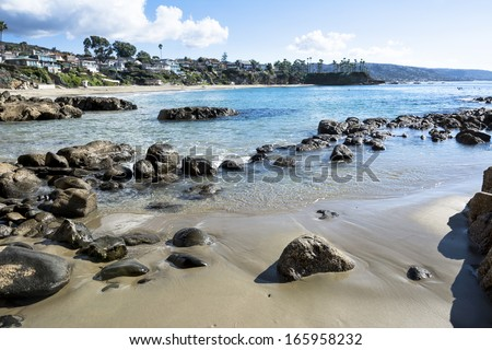 Beautiful beach cove in Laguna Beach, California shows its rugged shoreline and ocean front homes. - stock photo