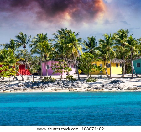 Beautiful beach of caribbean island with brilliant red, pink and yellow homes, Santo Domingo - stock photo