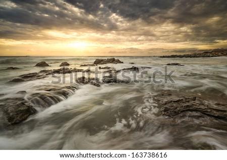 Beautiful beach photo, sea, dramatic clouds and stunning light - stock photo
